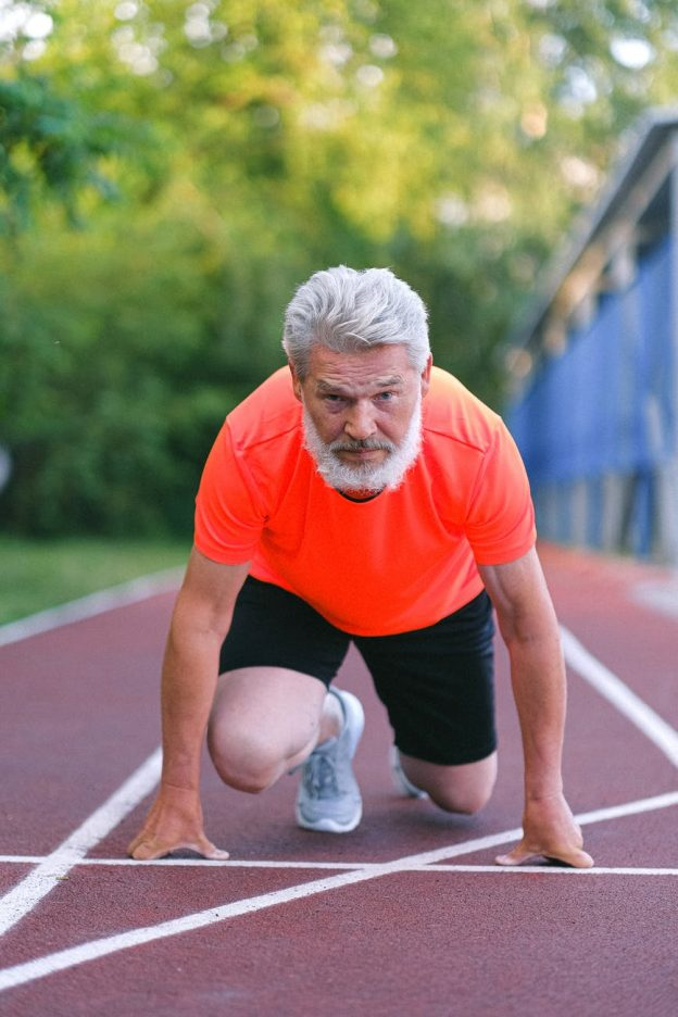 strong senior sportsman preparing for competition in racing